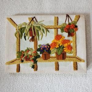 Vintage embroidered floral window scene.